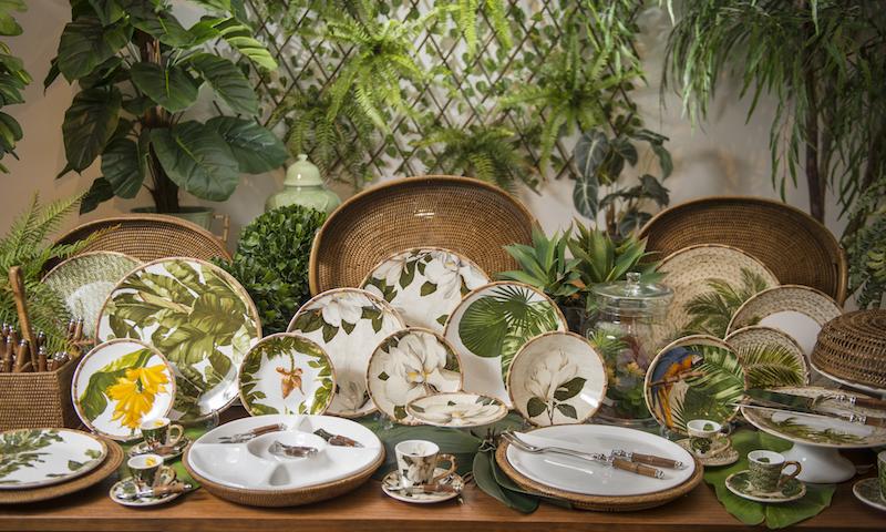 As folhas tropicais dos jogos de jantar Magnólia, Paraty, Iporanga e Trancoso formam uma floresta particular nesta composição de mesa posta.
