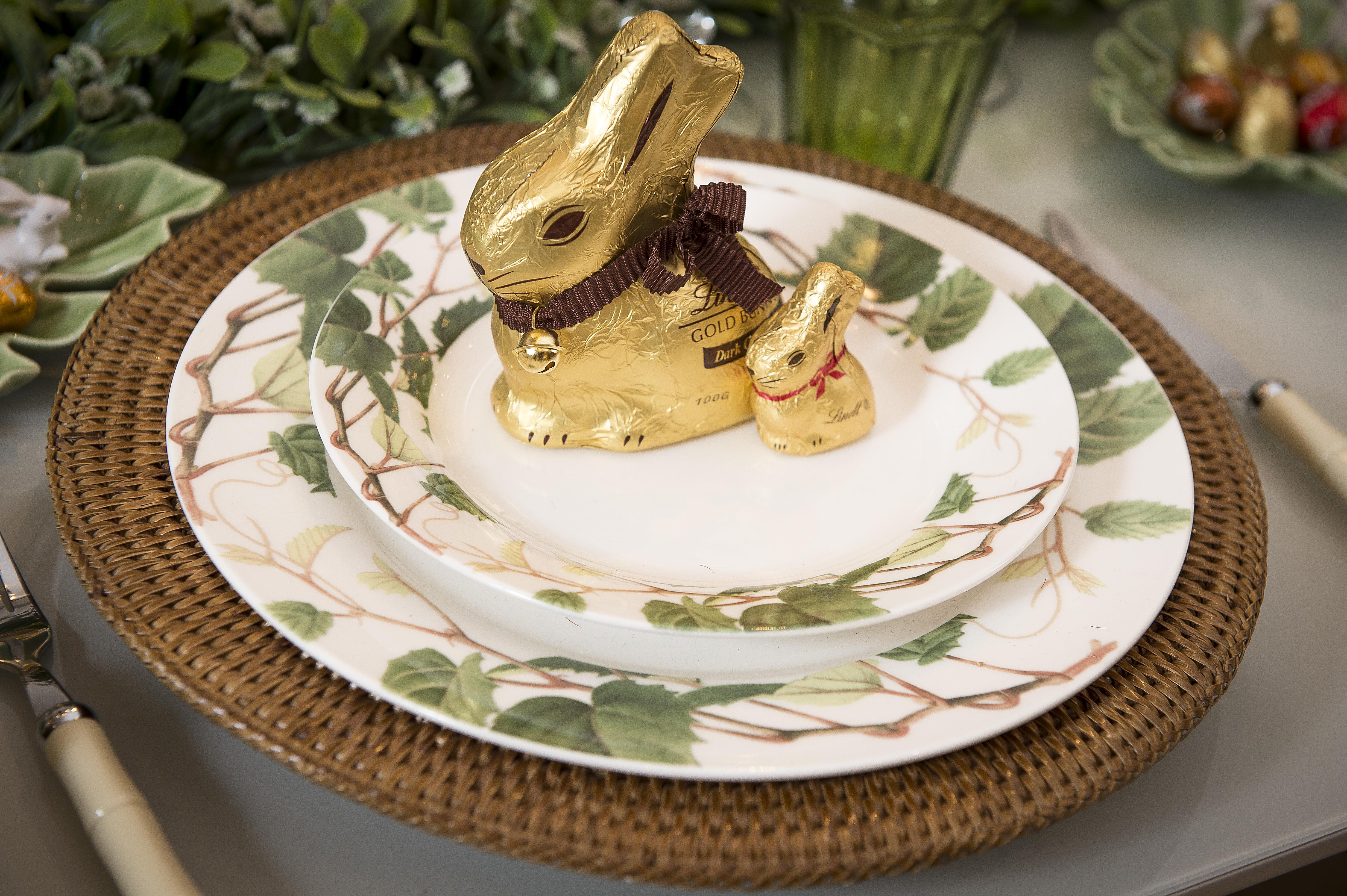 Sobre cada conjunto de pratos English Ivy, cada convidado ganha uma família de Bunnys Lindt, com mãe e filho. A presença do caminho de mesa de grama dispensa o jogo americano, substituindo por um sousplat de rattan.