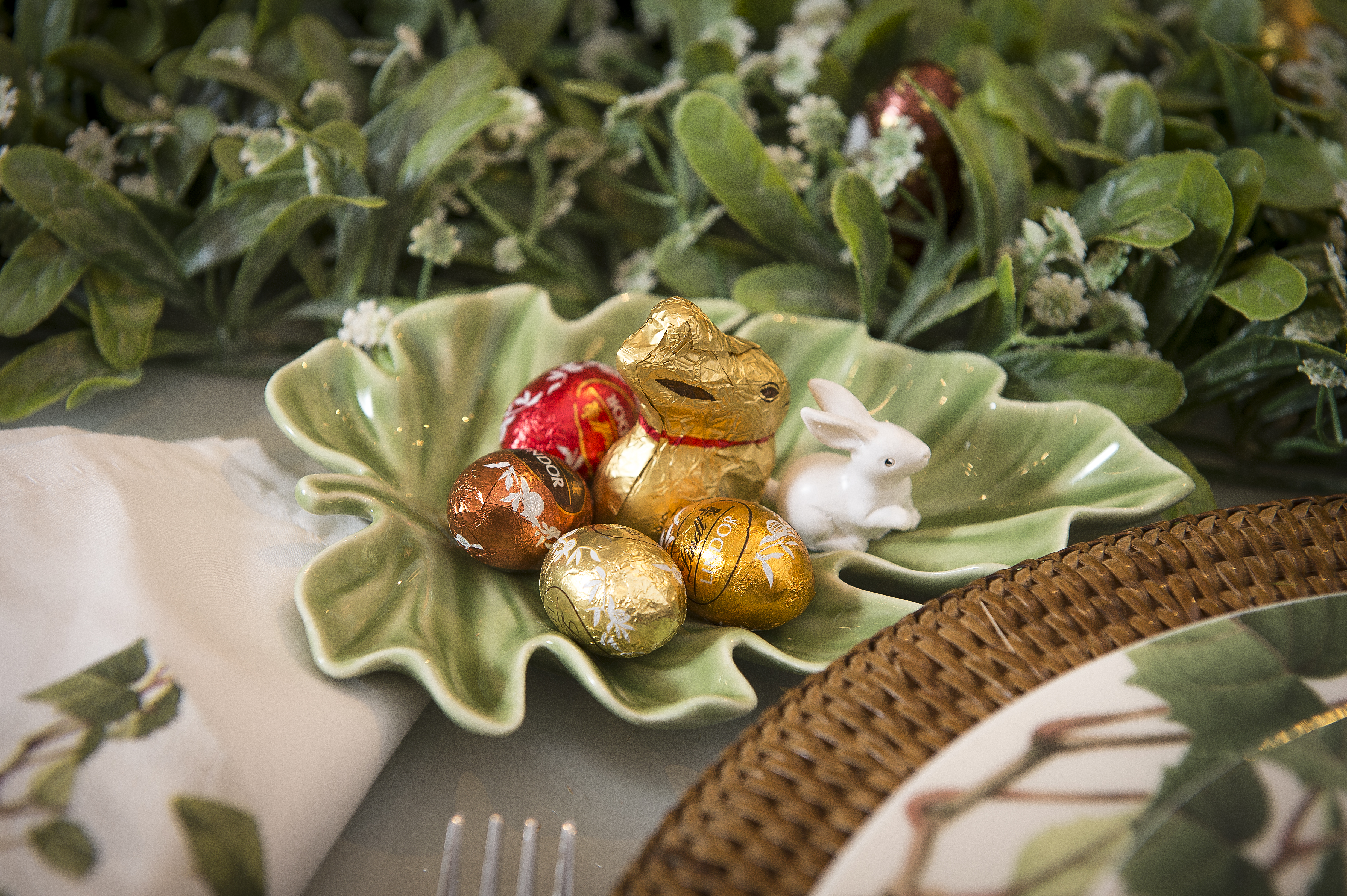"""Na frente de cada prato, uma gulodice super permitida na Páscoa: para os adultos não terem que participar da caça aos ovos com as crianças, uma pequena """"reserva de mercado"""" na folha de cerâmica. O coelho branco é de resina, e serve de guardião dos chocolates."""