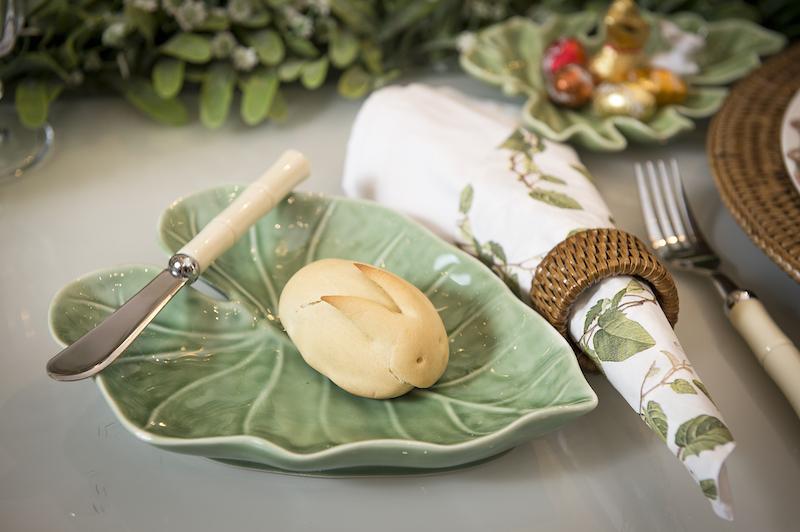 Ao lado de cada prato, uma folha de cerâmica faz o papel de pratinho de pão. O guardanapo de pano é forrado com um de papel combinando com a louça, aumentando a sensação de jardim da mesa.