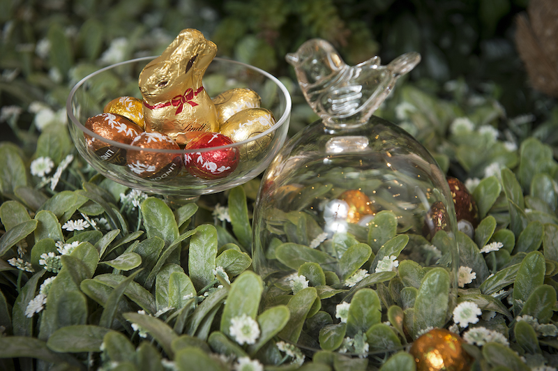Em meio ao verde, o prato de pé com tampa Bird, em vidro, serve de ninho para um coelho mini de chocolate (Lindt) e mini-ovinhos de vários sabores.