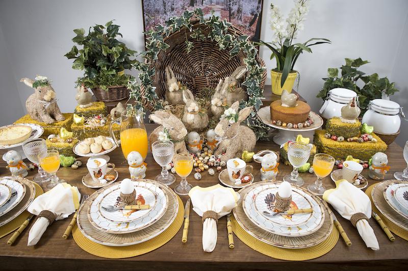 Uma mesa com jeiro de Páscoa no sítio, com muitos ovos e ninhos. De galinha e de coelhos.