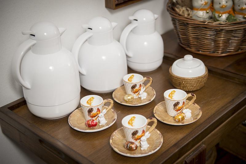 Aparador, garrafas térmicas, açucareiro em cerâmicacom base de rattan, mini-coelho em resina e xícaras de café linha Nest - Cecilia Dale