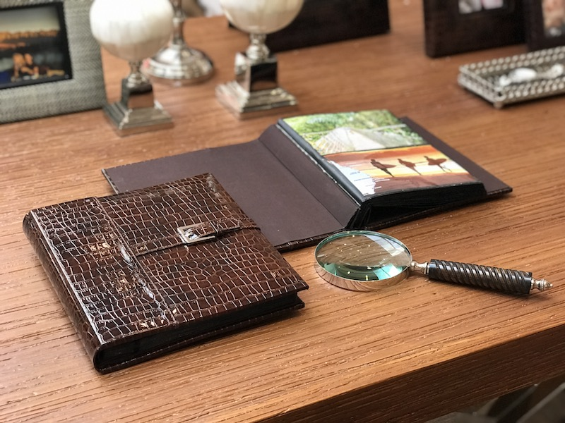 Álbum de fotos com acabamento em croco e lupa com cabo de madeira compõem a mesa do escritório - Cecilia Dale